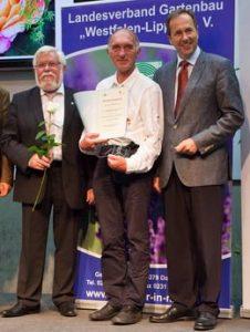Peter Marseile nimmt den Anerkennungspreis der Stadt Hamburg entgegen, mit ihm freuen sich Heinrich Hiep, Präsident des Landesverbandes Gartenbau Rheinland, links, und Helmut Rüskamp, Präsident des Landesverbandes Gartenbau Westfalen-Lippe