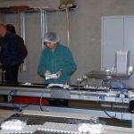 Hinter der Waage werden zu leichte oder zu schwere Schalen vom Band aussortiert, eine Mitarbeiterin gleicht das Manko von Hand aus und schickt die Schalen dann erneut über die Waage