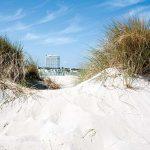 Blick auf das Hotel Neptun durch die Dünen mit dem berühmten feinen Sand der Ostsee