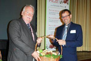 Michael Legrand, rechts, freut sich über einen großen Korb mit frischen Pilzen aus der Hand des BDC-Vorsitzenden Michael Schattenberg.