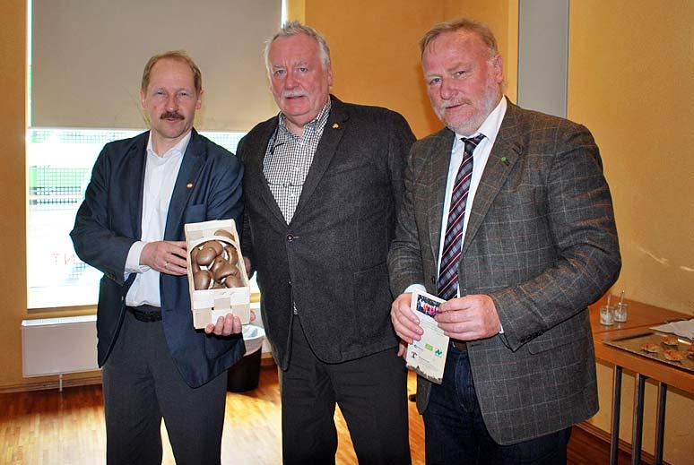 Dr. Behr nimmt ein Körbchen mit den begehrten braunen Champignons als Dankeschön aus den Händen vom BDC-Vorsitzenden Michael Schattenberg und Geschäftsführer Jochen Winkhoff gern an – von links nach rechts.