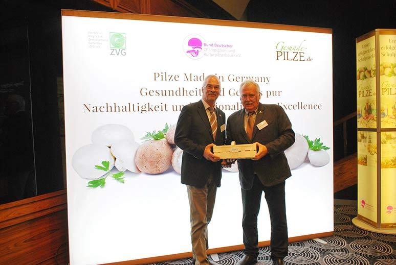 Joachim-Eberhard Maltzahn, links, nimmt aus den Händen des BDC-Vorsitzenden Michael Schattenberg ein Körbchen frischer Champignons als Dankeschön für sein Grußwort in Empfang.