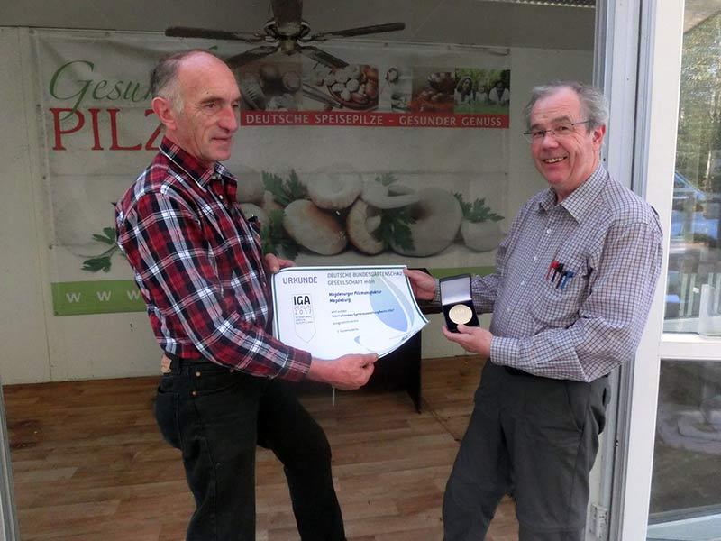 Dieter Völkers, Chef der Magdeburger Pilzmanufaktur, rechts, freut sich über die Bronzemedaille aus den Händen von Peter Marseille.